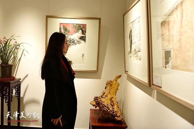 王紫萱女士在观赏展出的作品。
