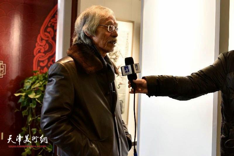 姚景卿先生在展览现场接受媒体采访。