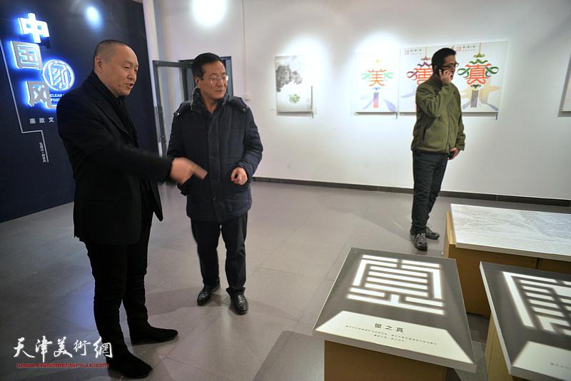 薛明与嘉宾在展览现场观看作品。