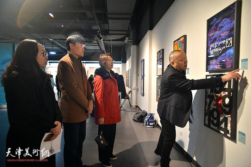 孙杰、薛明、王瑞雪在展览现场观看作品。