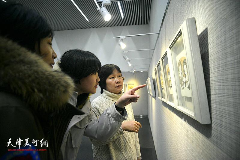 谢红在画展现场观看作品。