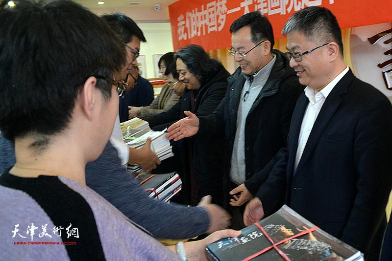 天津画院画家们为村民赠送画册。