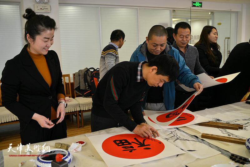 杨海涛在活动现场为村民写福字。