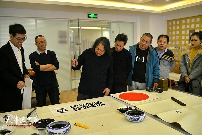 贾广健在活动现场为村民写书法。