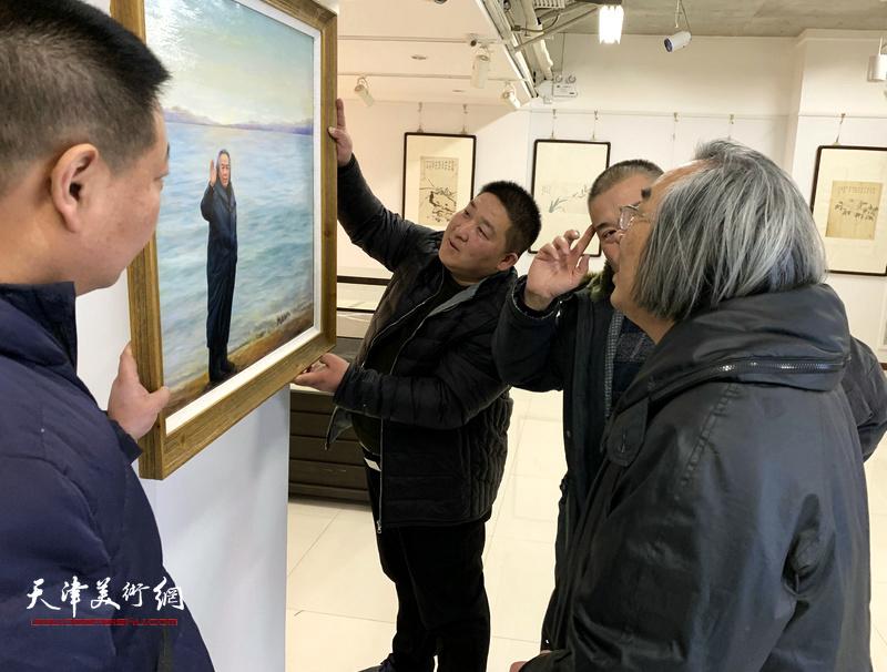 霍春阳仔细观赏写实油画《海边漫步》。