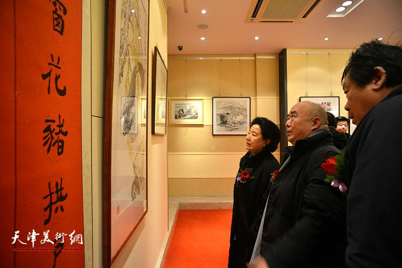 曹秀荣、尹沧海、郭鸿春在观看展出的作品。