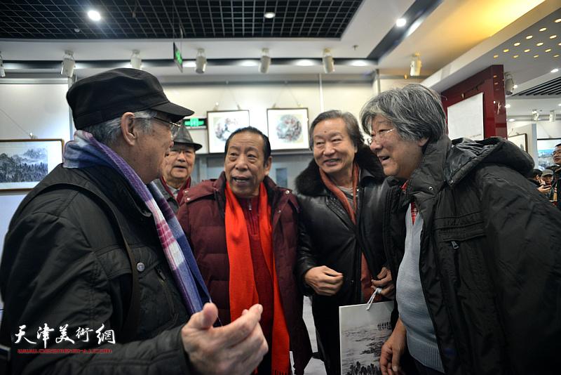 王山岭、刘家城、佟有为、张建国、邱贵杨在画展现场交谈。