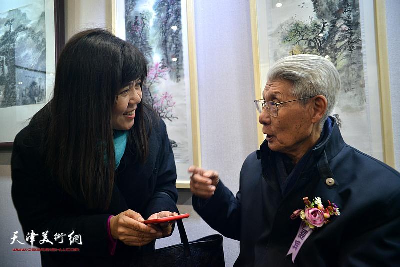 杨德树、王洪春在画展现场交谈。