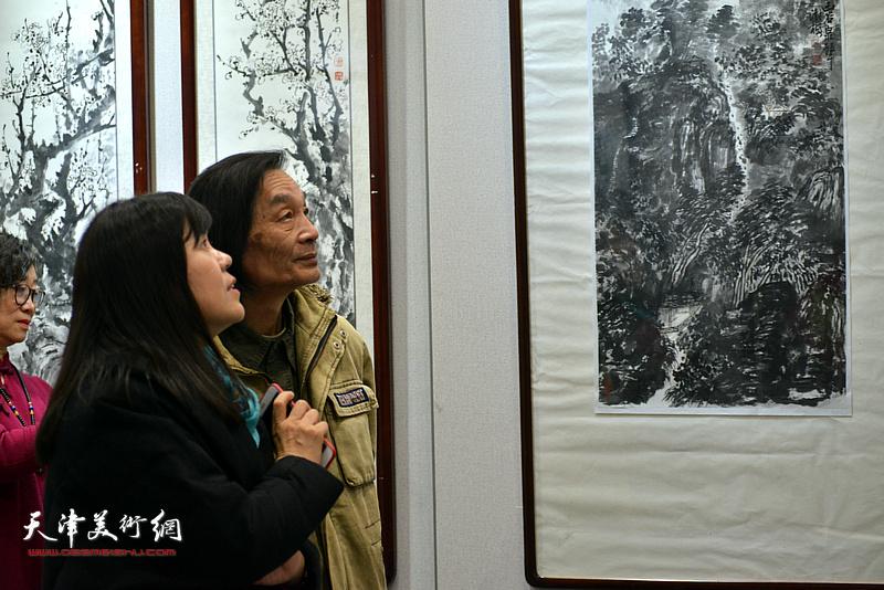田耀泉、王洪春在画展现场观看作品。