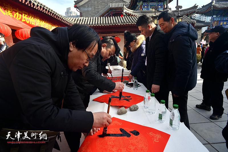王卫平、张晓彦在活动现场写福字。