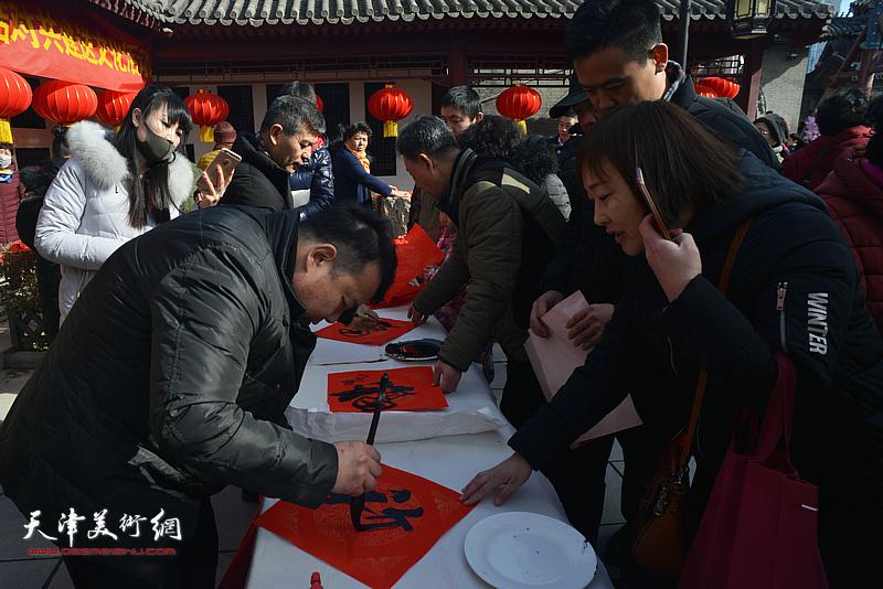 范扬、王卫平在活动现场写福字。