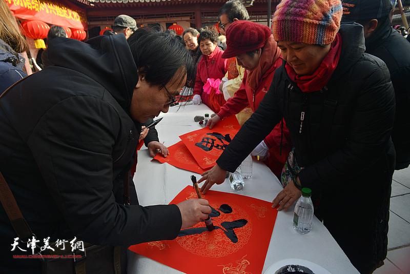 张晓彦在活动现场写福字。