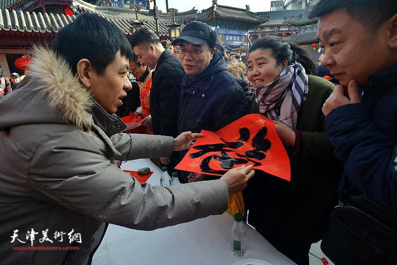 杨海涛在活动现场送福。