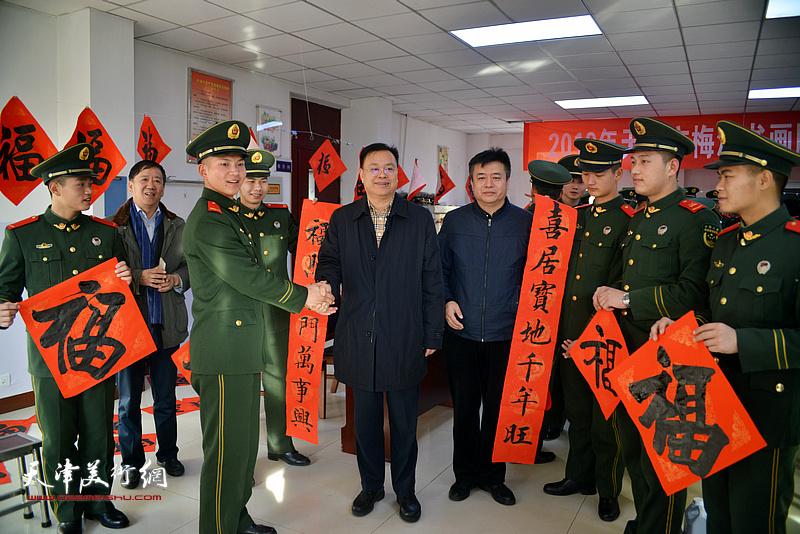 孙太利、郭志军、崔希鹏为武警官兵送福字、送春联。