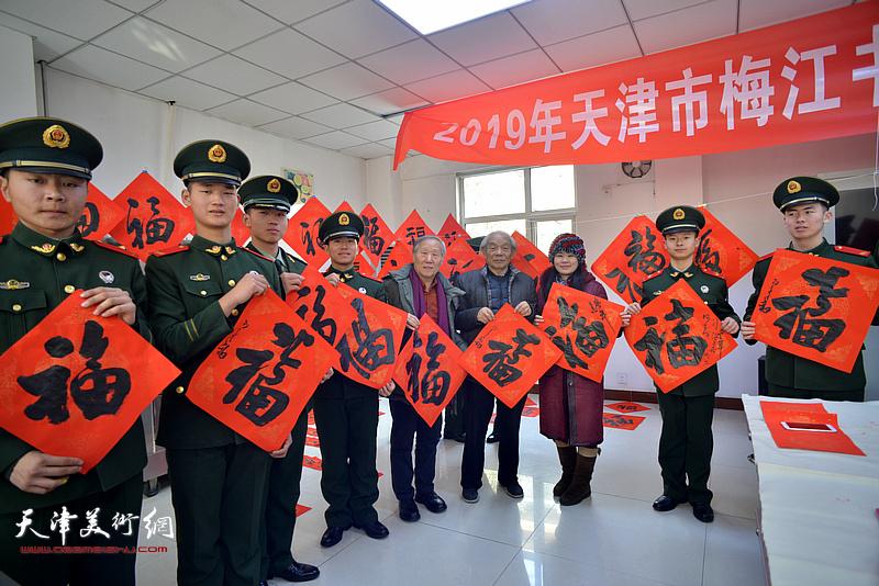 纪振民、姬俊尧、罗玉兰将福字送给武警战士。