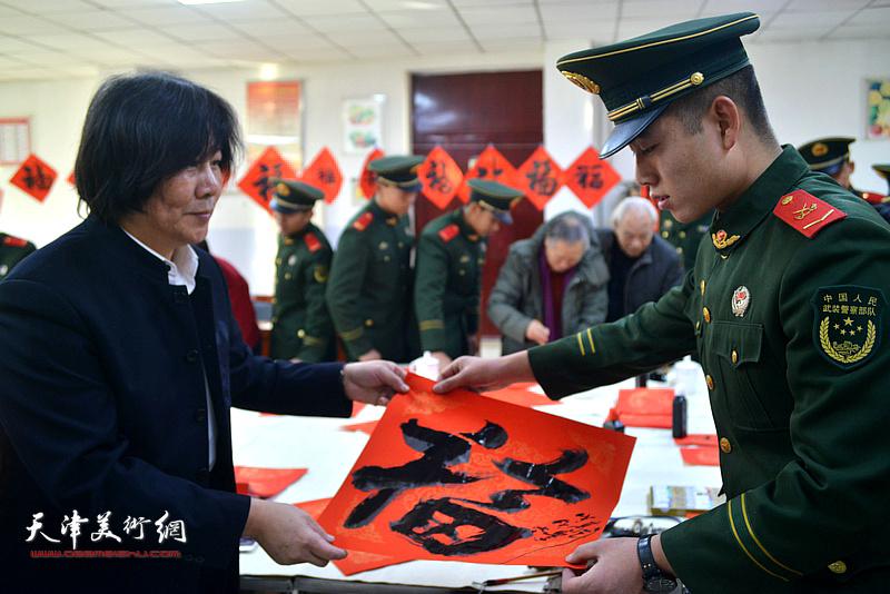 高学年将福字送给武警战士。