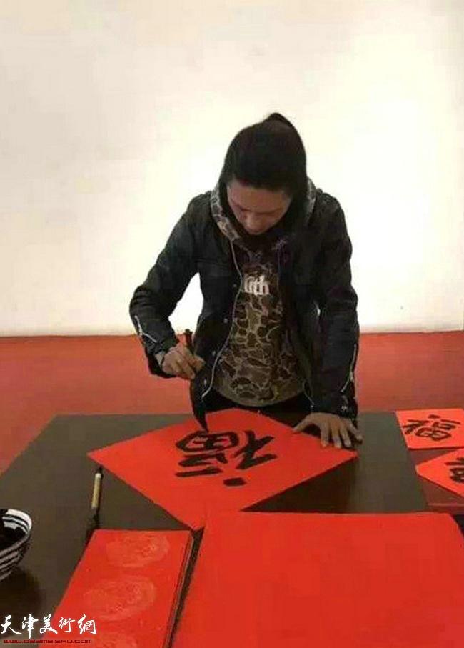 青年画家姚铸在送书画现场