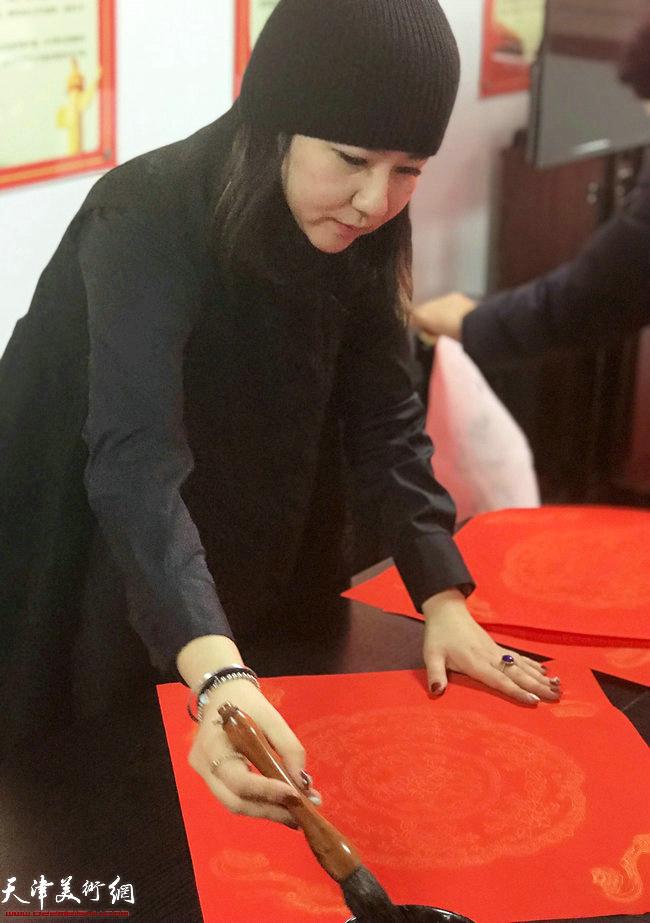 青年画家王霞在送书画现场
