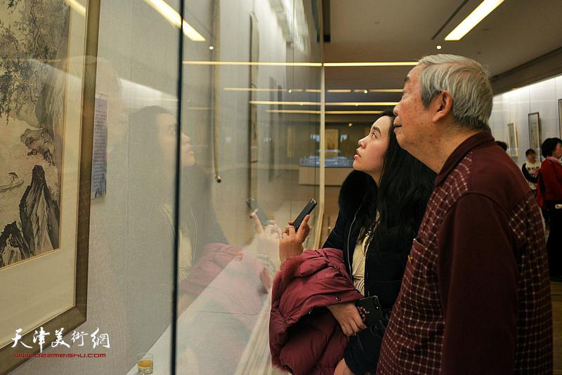 陈长智与外孙女严可馨观赏展出的陈少梅作品。