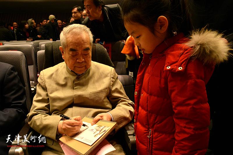 范曾在会场为小读者签名留念。