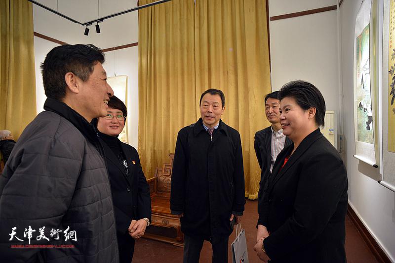 刘红、李响与嘉宾在画展现场交谈。