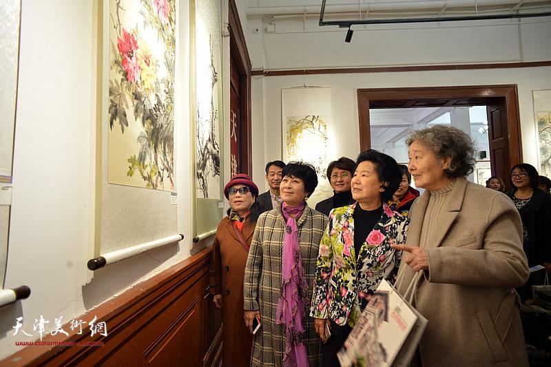 梦玉陪同曹秀荣观看作品。