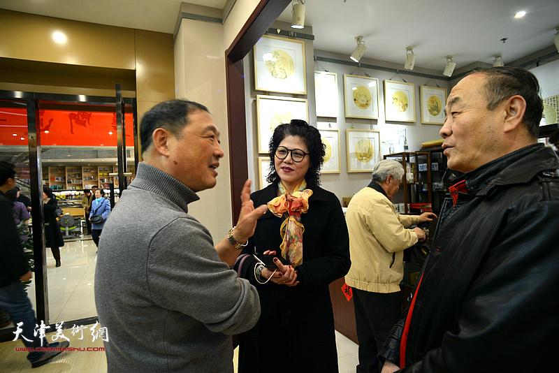 刘志君、陈德生、刘莉在书画展现场交流。