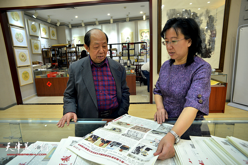 韩祖音、元林在阅览《华人艺术报》。