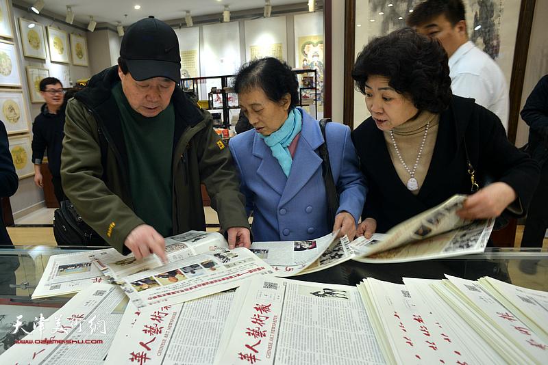 书画爱好者在阅览《华人艺术报》。