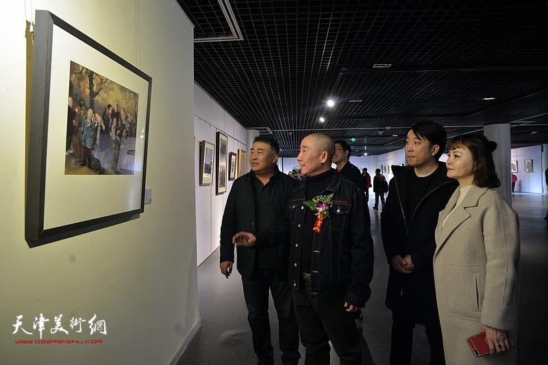 王再善向嘉宾介绍展出的作品。
