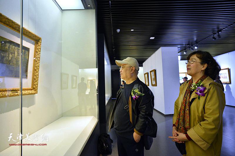 赵国经、王美芳在画展现场观看作品。