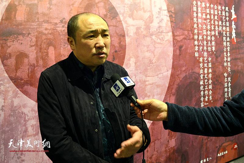 卢禹舜在画展现场接受媒体采访。