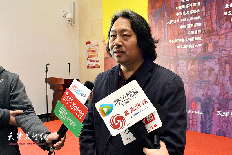 贾广健在画展现场接受媒体采访。
