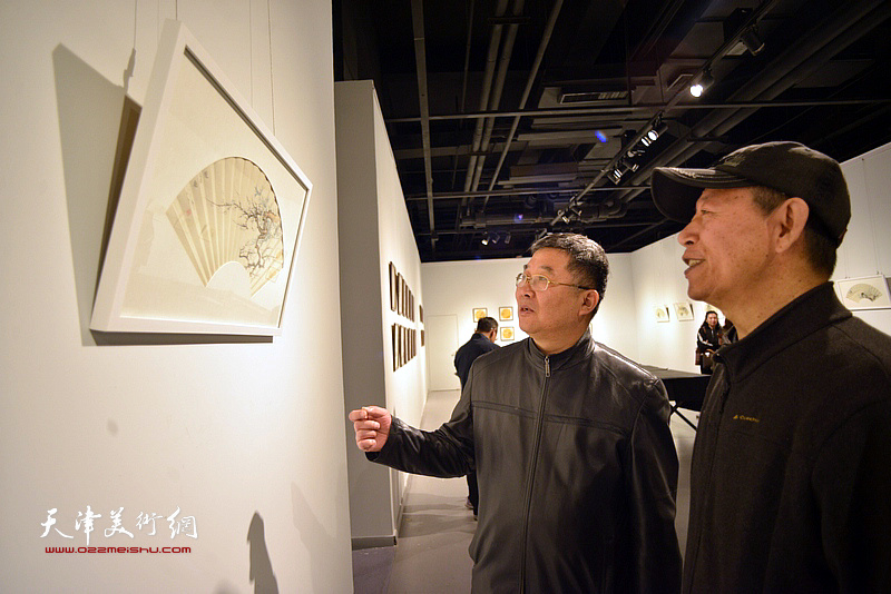 李延春、楚宝路在画展现场观看画作。