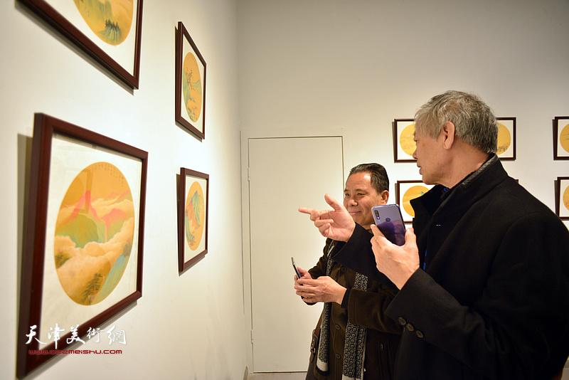 臧志建、赵树海在画展现场观看画作。