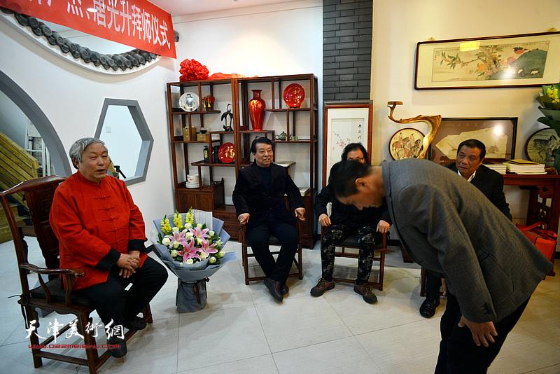 新弟子林广杰向恩师唐云来行礼。