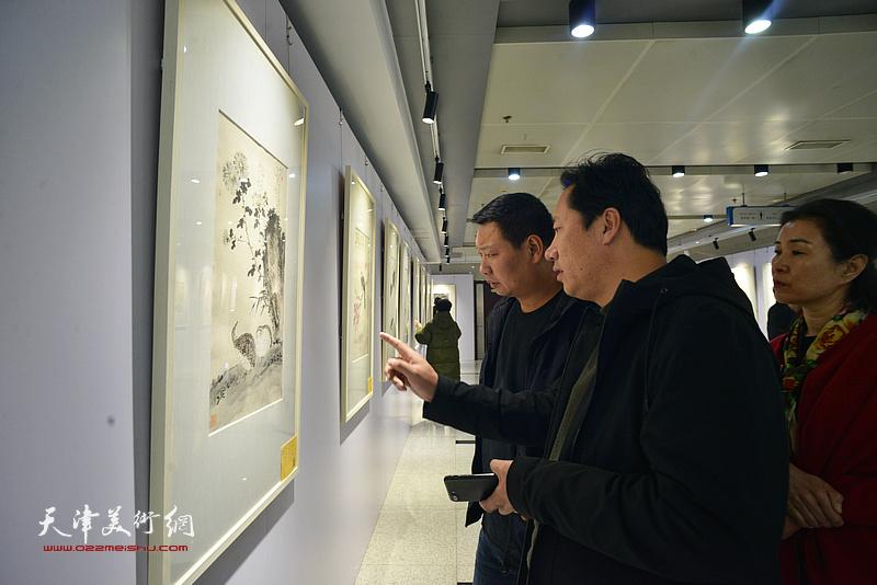王润、李亚在观看展出的作品。