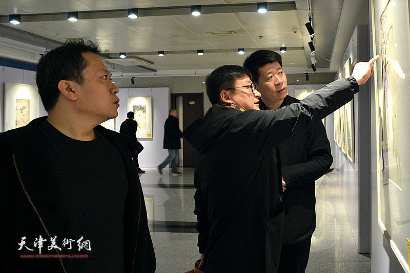 王蔚、孙飞、霍岩在观看展出的作品。