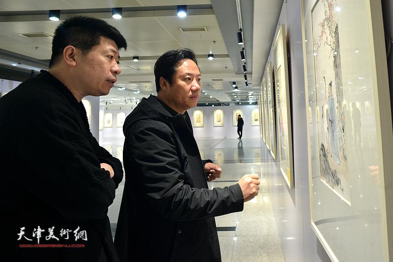 王蔚、李亚在观看展出的作品。