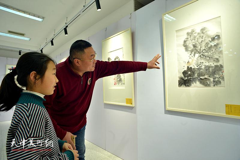 谭胜伟在画展现场给小画家讲画。