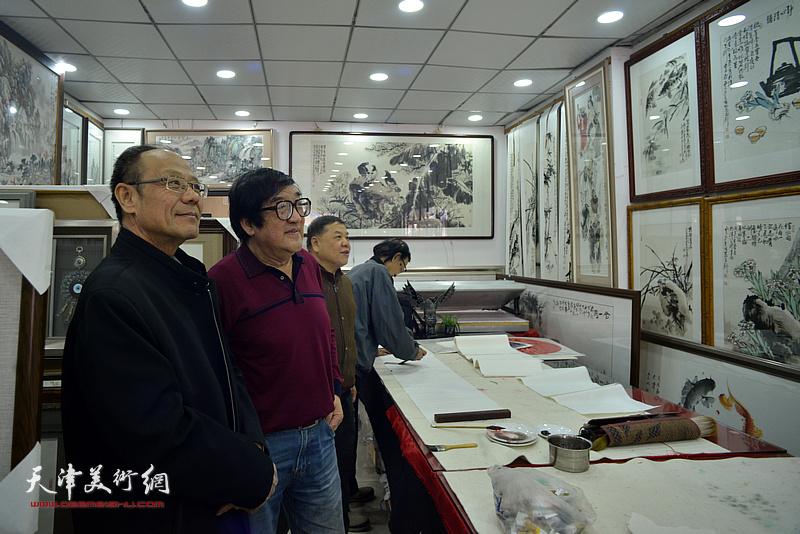 卢贵友陪同黄禄衡、董景波观赏展出的画作。