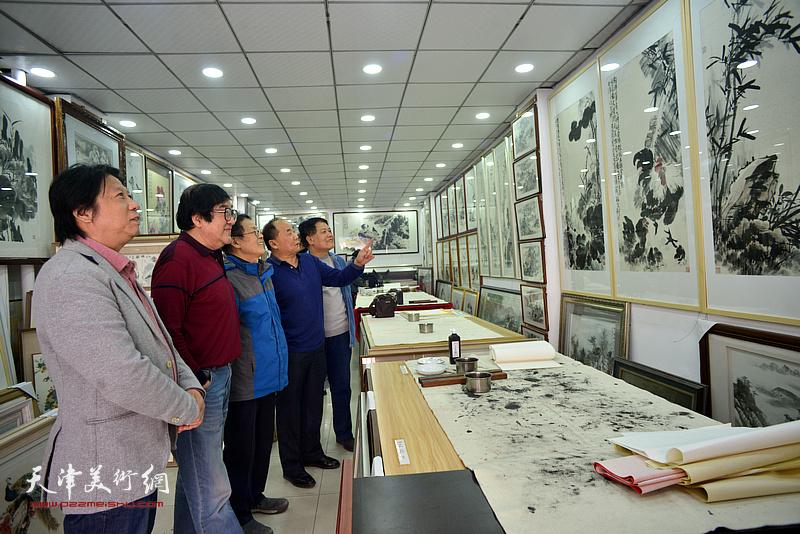 卢贵友陪同尚金声、李学亮、李建华观赏展出的画作。