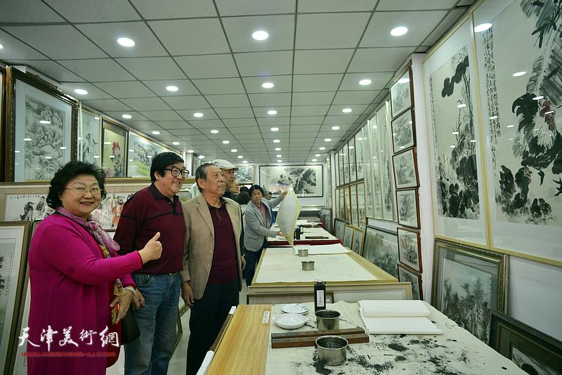 卢贵友陪同佟有为、于焕英、李嘉祥观赏展出的画作。