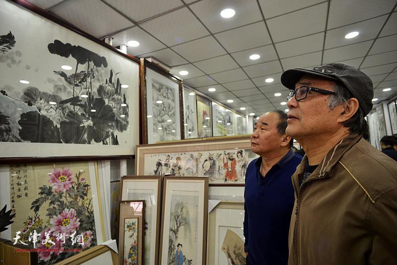 郭书仁、李建华观赏展出的画作。