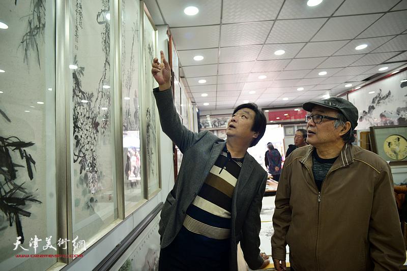 郭书仁、翟洪涛观赏展出的画作。