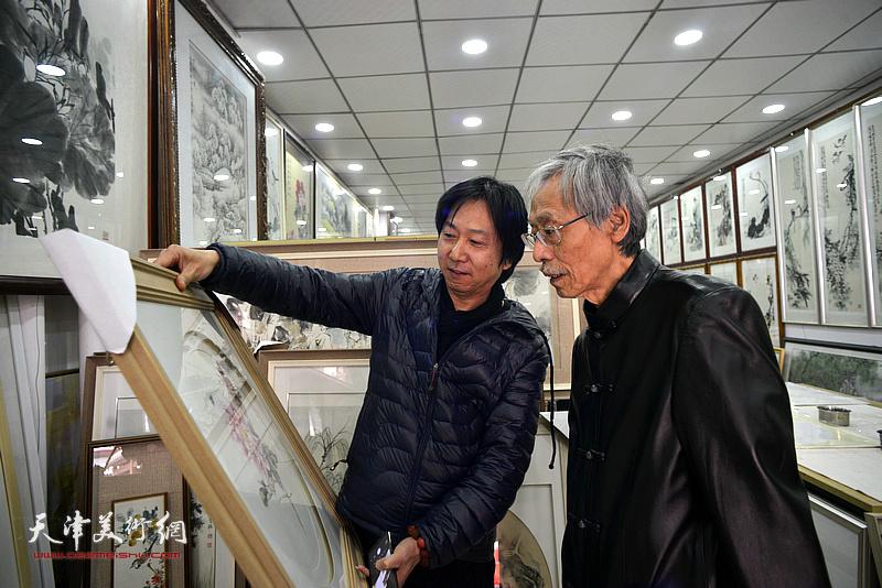 姚景卿、刘长利观赏展出的画作。