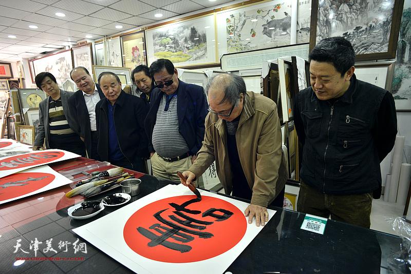郭书仁在画展现场写福寿。