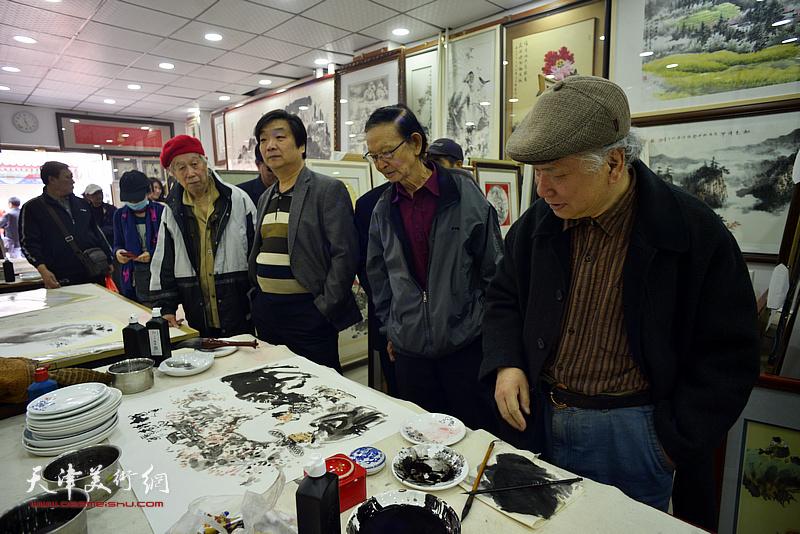 李风雨、房师武、翟洪涛在画展现场创作。
