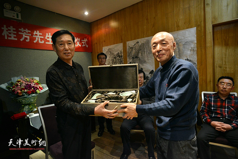 孙长文代表三位新弟子向老师钱桂芳赠送文具。