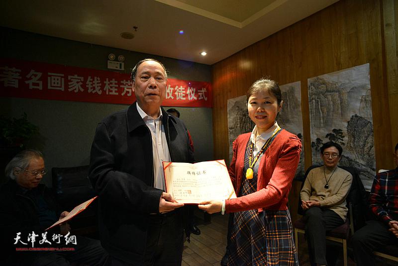 见证人郭凤祥向陈莉颁发拜师证书。